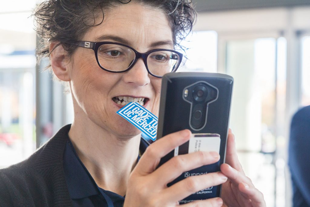 Woman in glasses uses her phone to take a photo