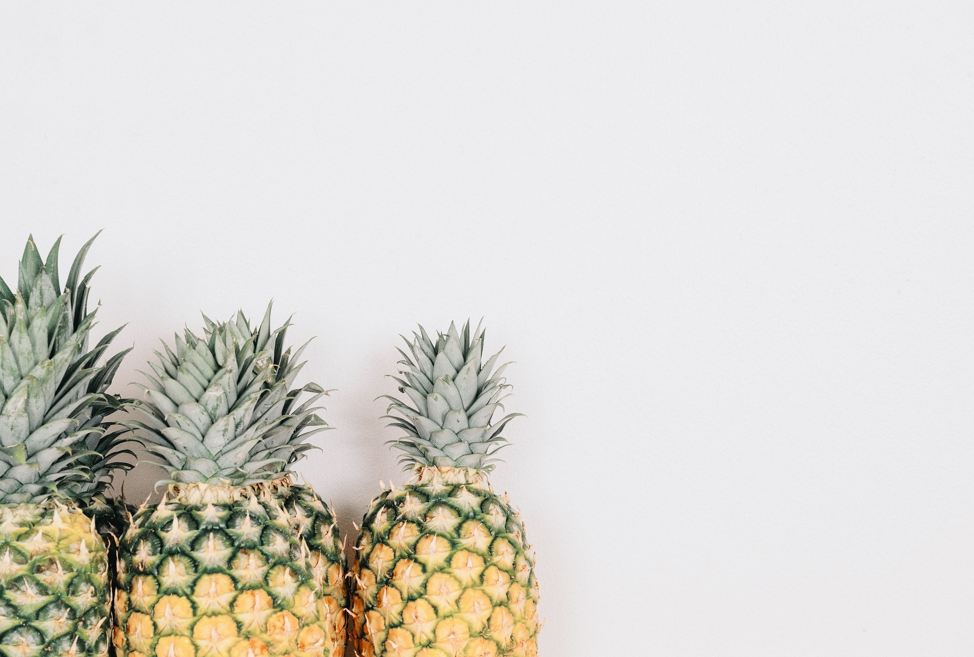 Three pineapples in descending size from left pictured in the lower left corner with blank white space all around.