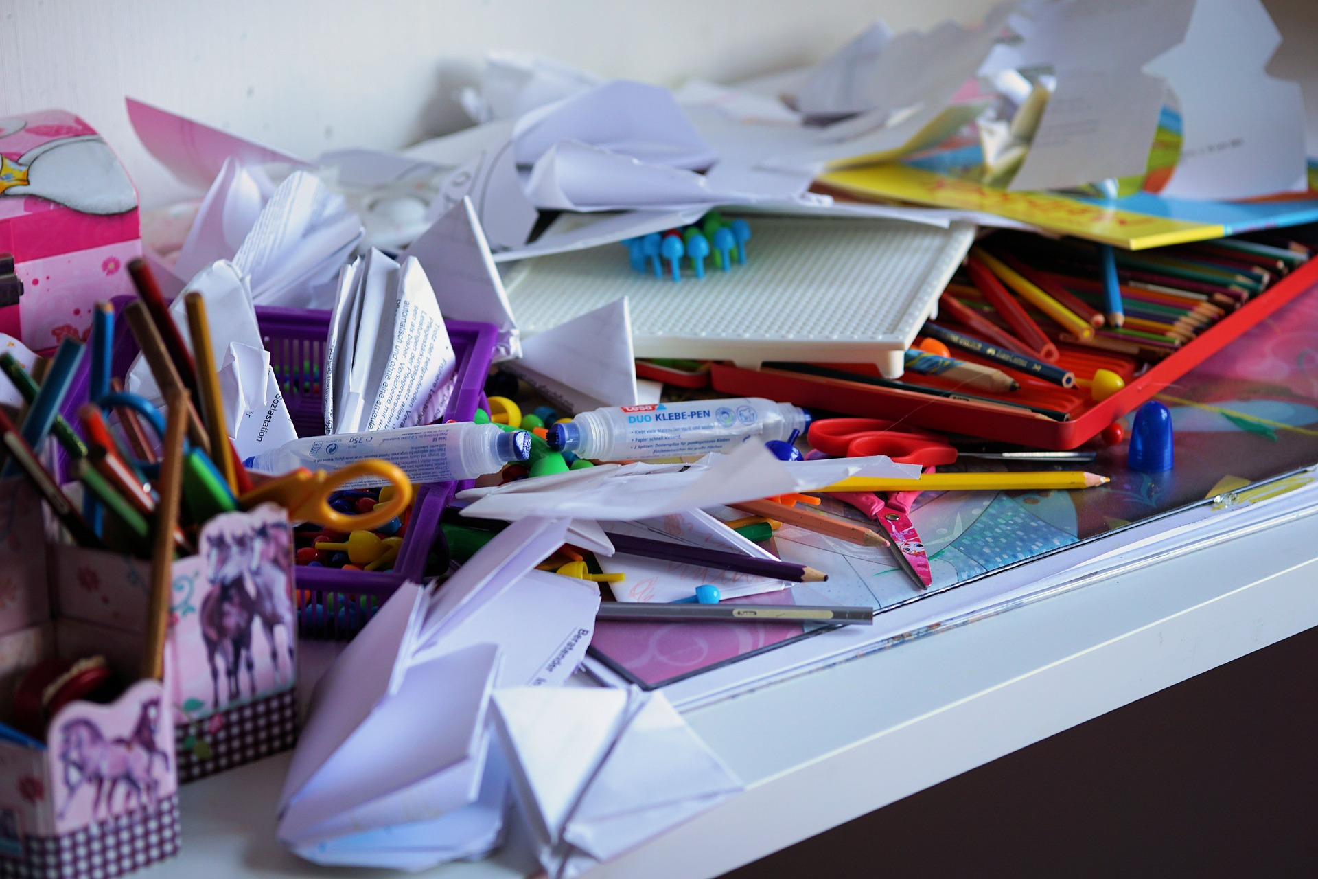 Papers and craft supplies cluttering the top of a white desk.